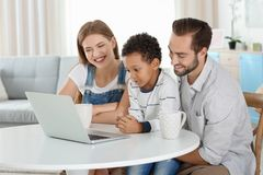 Happy couple with adopted African-American boy. Using laptop in living room Stock Photo