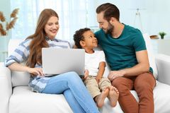 Happy couple with adopted African-American boy. Using laptop while sitting on couch at home Royalty Free Stock Images