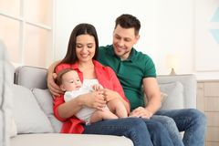 Happy couple with adorable baby on sofa at home royalty free stock image