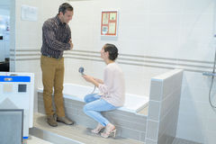 Happy couple adults choosing bathroom faucets in plumbing store Royalty Free Stock Photography