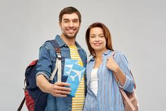 Happy couple with air tickets, bags and passport. Travel, tourism and vacation concept - happy couple with air tickets, bags and passport over grey background royalty free stock image