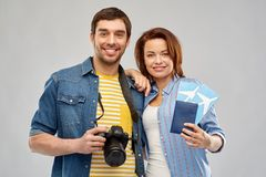 Happy couple with air tickets, passport and camera. Travel, tourism and vacation concept - happy couple with air tickets, passport and camera over grey royalty free stock photos