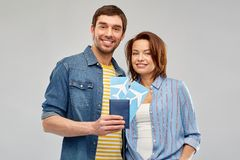 Happy couple with air tickets and passport. Travel, tourism and vacation concept - happy couple with air tickets and passport over grey background stock photos