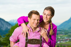 Happy couple in Alpine meadow in Tracht Stock Image