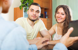 Happy couple answer questions. Of outreach worker with laptop at table in office Stock Image