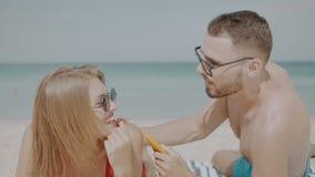 Beautiful couple during summer holidays. Happy couple applying sun tanning lotion on the beach, man putting sunscreen suntan cream on woman stock video footage