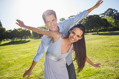 Happy couple with arms outstretched at park Royalty Free Stock Image