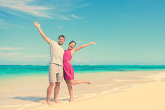 Happy Couple With Arms Raised Standing At Beach Royalty Free Stock Images