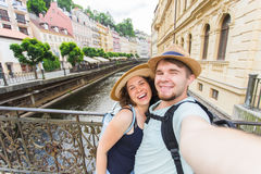 Happy couple, attractive woman and man walking in city and enjoying romance. Lovers making selfie and smiling. Tourists Stock Photos