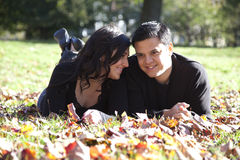 Happy couple in autumn park in love. Happy young couple relaxing in a fall park stock photos