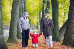 Happy couple in autumn park with toddler girl Stock Photos