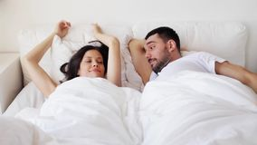 Happy couple awakening in bed at home. People, rest, sleeping and relationships concept - happy couple awakening in bed at home stock video