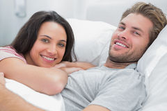Happy couple awaking and looking at camera Stock Photos