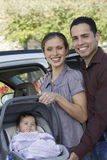 Happy Couple With Baby In Carrier Stock Images