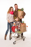 Happy couple and baby in shopping cart Royalty Free Stock Image