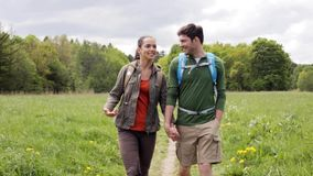 Happy couple with backpacks hiking outdoors 3. Travel, hiking, backpacking, tourism and people concept - happy couple with backpacks holding hands and walking stock video