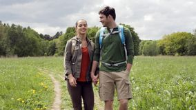 Happy couple with backpacks hiking outdoors 4. Travel, hiking, backpacking, tourism and people concept - happy couple with backpacks holding hands and walking stock footage
