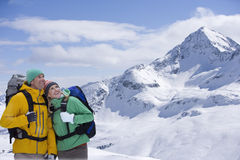 Happy couple with backpacks looking up at sky on snowy mountain Stock Photography