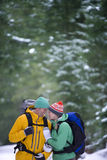 Happy couple with backpacks smiling face to face in snowy woods Royalty Free Stock Photos
