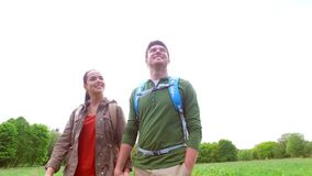 Happy couple with backpacks walk on country road 1. Travel, hiking, backpacking, tourism and people concept - happy couple with backpacks holding hands and stock video