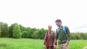 Happy couple with backpacks walk on country road 3. Travel, hiking, backpacking, tourism and people concept - happy couple with backpacks holding hands and stock video