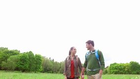 Happy couple with backpacks walk on country road 5. Travel, hiking, backpacking, tourism and people concept - happy couple with backpacks holding hands and stock video footage