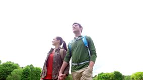 Happy couple with backpacks walking outdoors 6. Travel, hiking, backpacking, tourism and people concept - happy couple with backpacks holding hands and walking stock footage