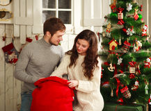 Happy couple with bag of gifts on Christmas tree at home Royalty Free Stock Photography