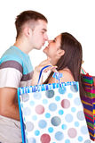 Happy couple with bags kissing Stock Photography