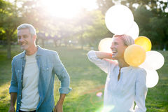 Happy couple with balloons at the park Royalty Free Stock Photos