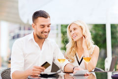 Happy couple with bank card and bill at restaurant. Date, people, payment and relations concept - happy couple with credit card, bill and wine glasses at stock photos