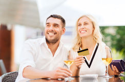 Happy couple with bank card and bill at restaurant. Date, people, payment and relations concept - happy couple with credit card, bill and wine glasses at royalty free stock image