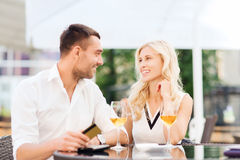 Happy couple with bank card and bill at restaurant. Date, people, payment and relations concept - happy couple with credit card, bill and wine glasses at stock image