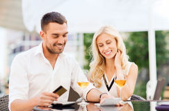 Happy couple with bank card and bill at restaurant. Date, people, payment and relations concept - happy couple with credit card, bill and wine glasses at stock photography