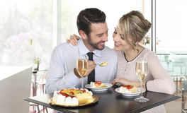 Happy couple at the bar with champagne and fruit cake, love Royalty Free Stock Images