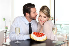 Happy couple at the bar with sparkling wine and cake, love conce Stock Images