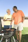 Happy Couple Barbecuing In Lawn Royalty Free Stock Photography