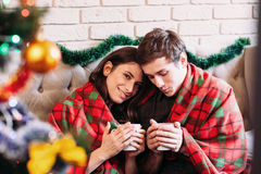 Happy couple basking with hot chocolate and tartan Stock Image