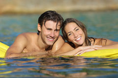 Happy couple bathing on the beach in summer vacation. With a perfect white smile and looking at camera Royalty Free Stock Photography