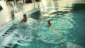 Happy couple bathing at luxury spa. Relaxed family resting in whirlpool bath stock video footage
