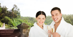 Happy couple in bathrobes with champagne at resort Royalty Free Stock Photos