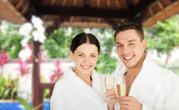 Happy couple in bathrobes with champagne at resort. People, travel, tourism, vacation and holidays concept - happy couple in bathrobes with champagne glasses stock image