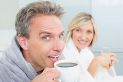 Happy couple in bathrobes with coffee cup and juice Royalty Free Stock Images