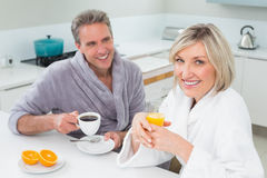 Happy couple in bathrobes having breakfast in kitchen Stock Photos
