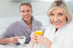 Happy couple in bathrobes having breakfast Royalty Free Stock Photo