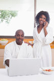 Happy couple in bathrobes in the kitchen using technology Stock Photography