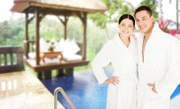 Happy couple in bathrobes over spa hotel resort Royalty Free Stock Image