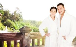 Happy couple in bathrobes over spa hotel resort Royalty Free Stock Photo