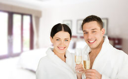 Happy couple in bathrobes over spa hotel room Stock Photo
