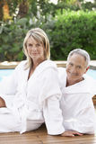 Happy Couple In Bathrobes Sitting By Pool. Portrait of happy middle aged couple in bathrobes sitting by pool Stock Photo